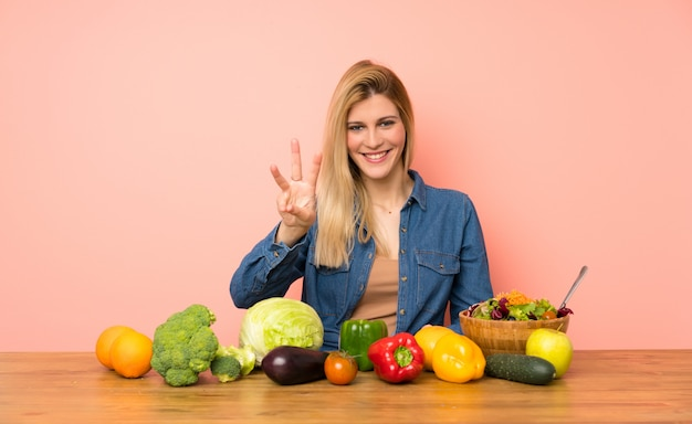 Young blonde woman with many vegetables happy and counting three with fingers