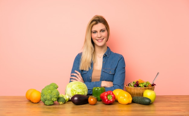 Young blonde woman with many vegetables keeping the arms crossed in frontal position