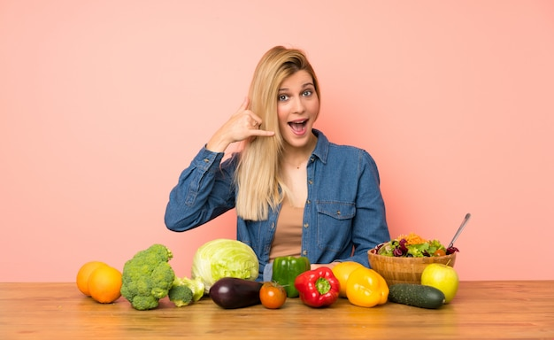 Young blonde woman with many vegetables making phone gesture. call me back sign