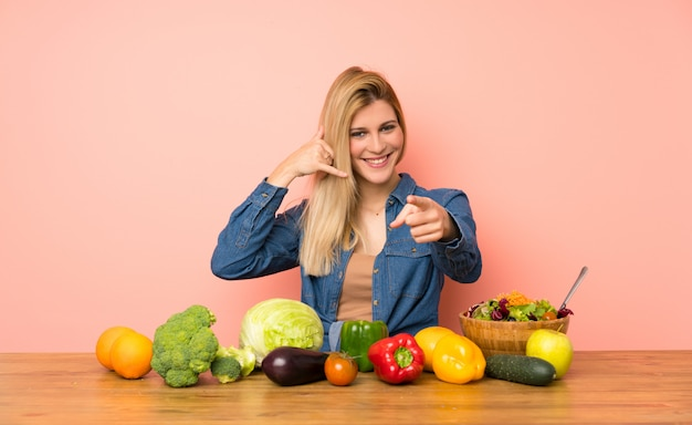 Young blonde woman with many vegetables making phone gesture and pointing front