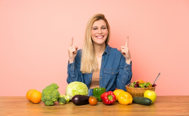 Young blonde woman with many vegetables pointing up a great idea