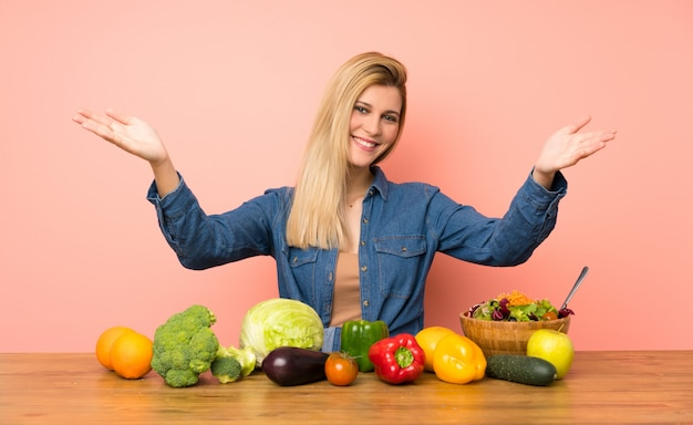 Young blonde woman with many vegetables presenting and inviting to come with hand