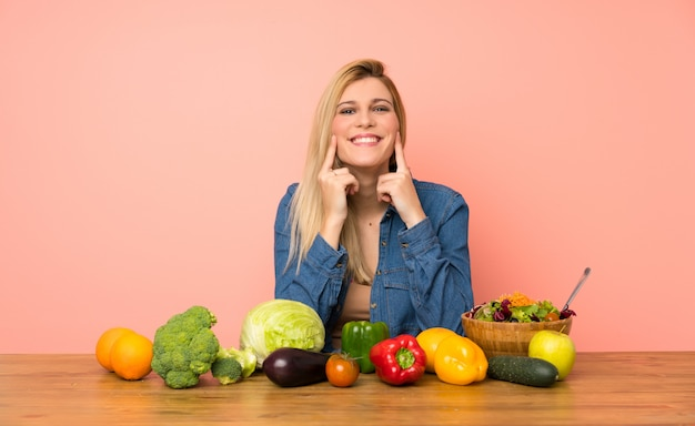 Young blonde woman with many vegetables smiling with a happy and pleasant expression
