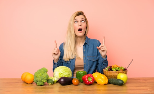 Young blonde woman with many vegetables surprised and pointing up