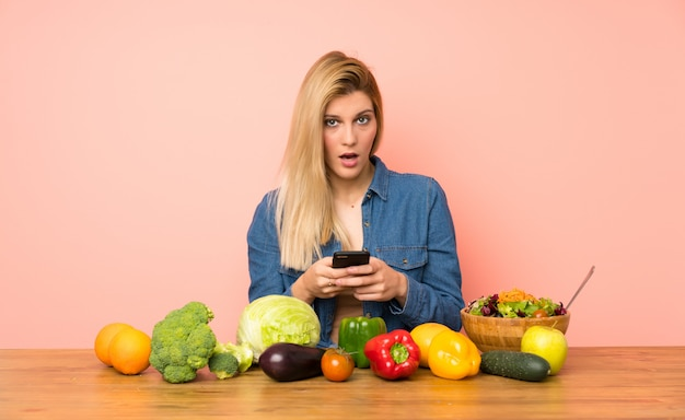 Young blonde woman with many vegetables surprised and sending a message