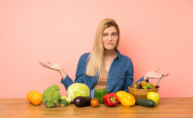 Young blonde woman with many vegetables unhappy for not understand something