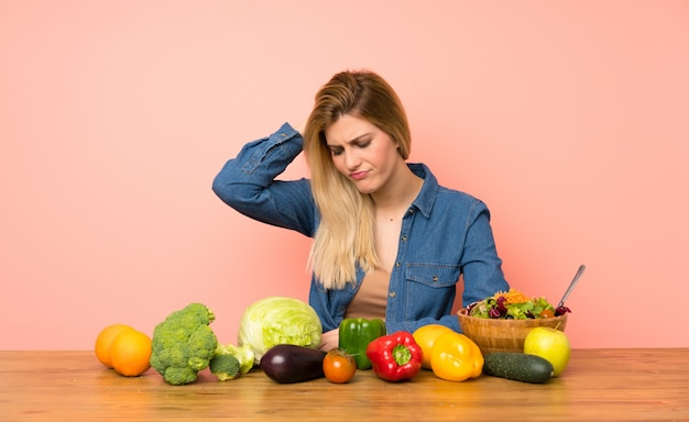 Young blonde woman with many vegetables with an expression of frustration and not understanding