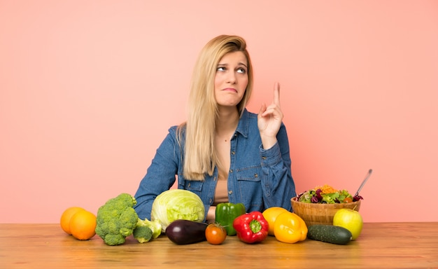Young blonde woman with many vegetables with fingers crossing and wishing the best