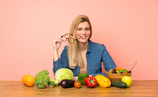 Young blonde woman with many vegetables with glasses and happy