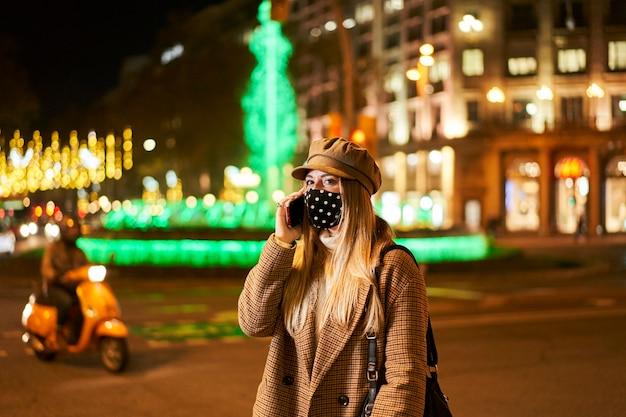밤에 도시에서 전화 통화하는 마스크와 젊은 금발 여자. 겨울 분위기.