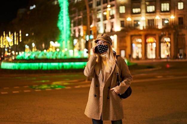 밤에 야외에서 전화 통화하는 마스크와 젊은 금발의 여자. 배경에는 많은 도시의 불빛이 있습니다. 겨울 분위기.