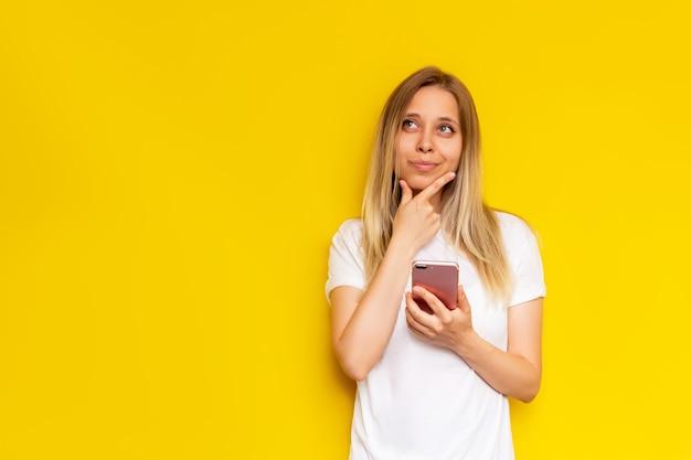 Молодая блондинка с мобильным телефоном думает, глядя в сторону на желтом фоне
