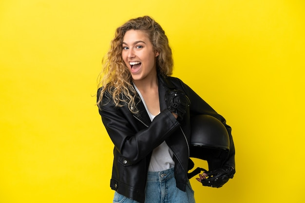 Young blonde woman with a motorcycle helmet isolated on yellow background celebrating a victory