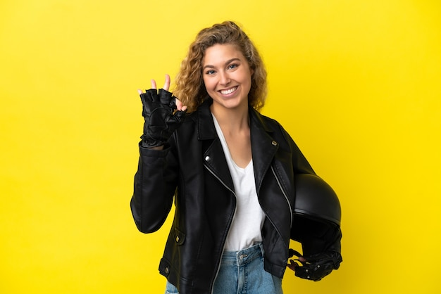 Young blonde woman with a motorcycle helmet isolated on yellow background showing ok sign with fingers