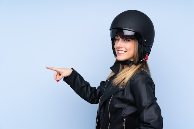 Young blonde woman with a motorcycle helmet and pointing to the lateral over isolated blue wall