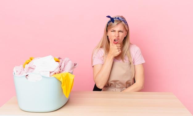 Молодая блондинка женщина с широко открытыми глазами и ртом и рукой за подбородок. концепция стирки одежды