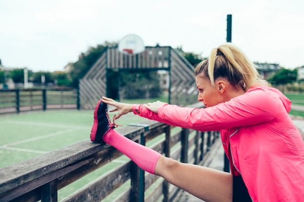 Young blonde woman with pigtail stretching her legs before training outdoors
