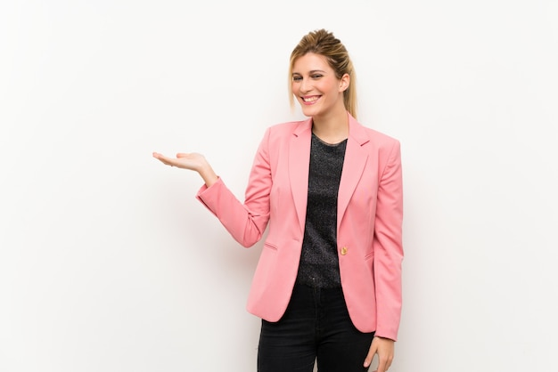 Young blonde woman with pink suit holding copyspace imaginary on the palm to insert an ad