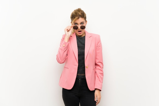 Young blonde woman with pink suit with glasses and surprised