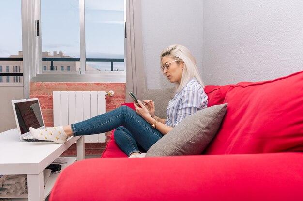 백금 머리와 안경 젊은 금발의 여자는 그녀의 휴대 전화를 사용하여 스트라이프 셔츠를 입고. 소파에 앉아. 휴식 시간.