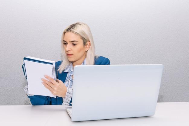 青いブレザーに身を包んだプラチナの髪の若いブロンドの女性が、自宅からノートパソコンを持って在宅勤務し、議題を書いています。在宅勤務の概念。