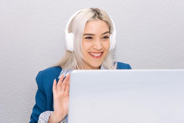 ノートパソコンとヘッドセットを使用して自宅から在宅勤務の青いブレザーに身を包んだプラチナの髪の若いブロンドの女性。在宅勤務の概念。