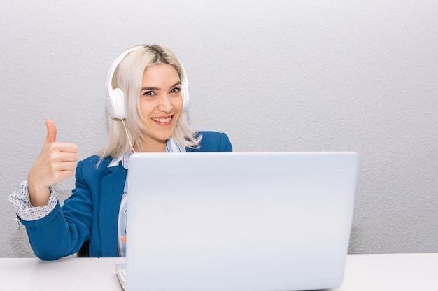 Молодая блондинка с платиновыми волосами, одетая в синий пиджак, удаленно работает дома с ноутбуком и наушниками. концепция удаленной работы.