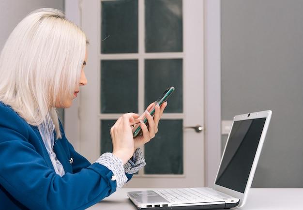 Молодая блондинка с платиновыми волосами, одетая в синий пиджак, удаленно работает дома с телефоном и ноутбуком. концепция удаленной работы. вид сбоку