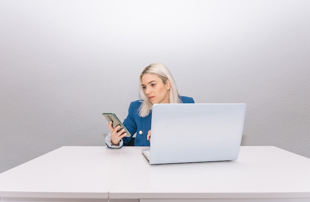 Молодая блондинка с платиновыми волосами, одетая в синий пиджак, удаленно работает дома с телефоном и ноутбуком. концепция удаленной работы.