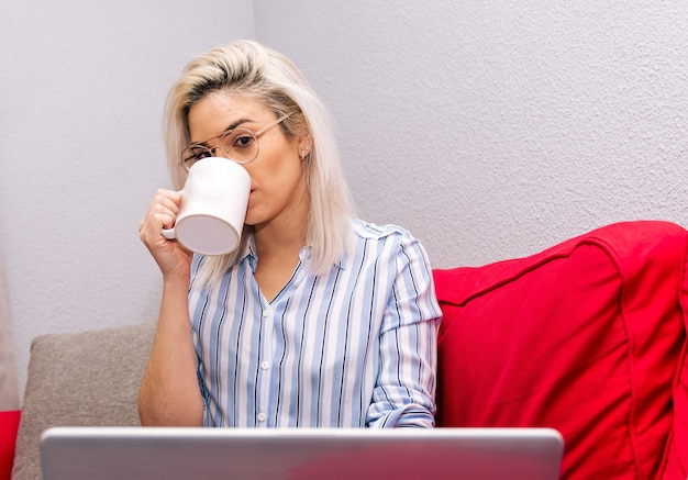 Young blonde woman with platinum hair and eyeglasses dressed with a striped shirt drinking a cup of tea and using her laptop. sitting on the couch. relax time.