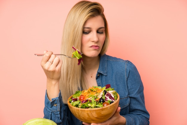 Young blonde woman with salad