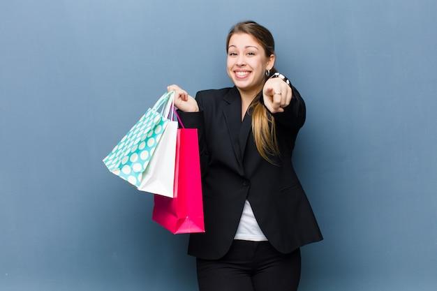 グランジ壁背景に買い物袋を持つ若いブロンドの女性