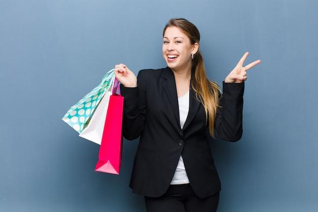 グランジ壁に買い物袋を持つ若いブロンドの女性
