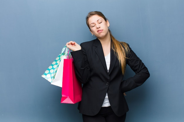 グランジの壁に買い物袋を持つ若いブロンドの女性