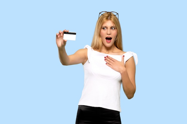 Young blonde woman with troubled holding broken smartphone on isolated blue background