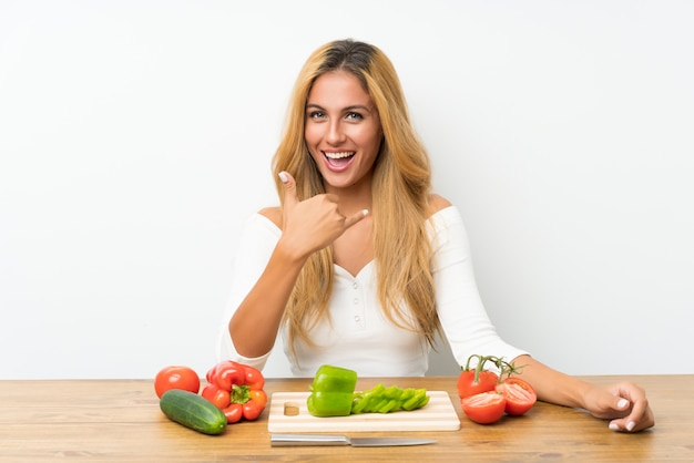 Young blonde woman with vegetables in a table making phone gesture