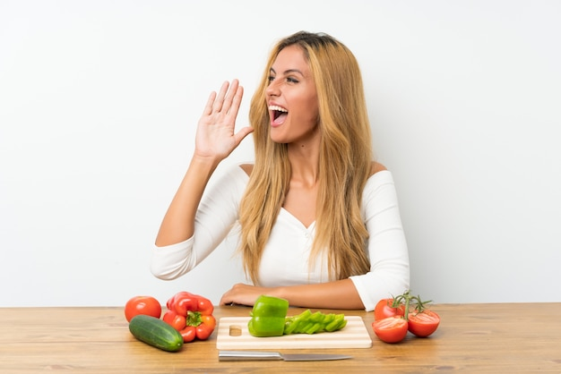 Young blonde woman with vegetables in a table shouting with mouth wide open