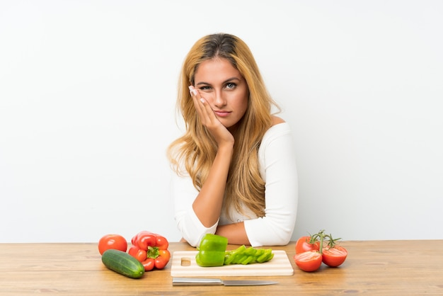 Young blonde woman with vegetables in a table unhappy and frustrated
