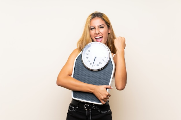 Young blonde woman with weighing machine over isolated wall