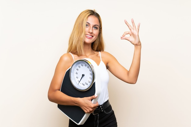 Young blonde woman with weighing machine making ok sign