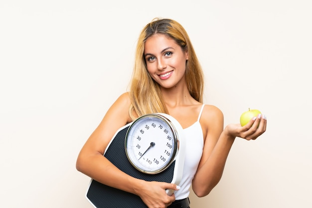 Young blonde woman with weighing machine and with an apple over isolated wall