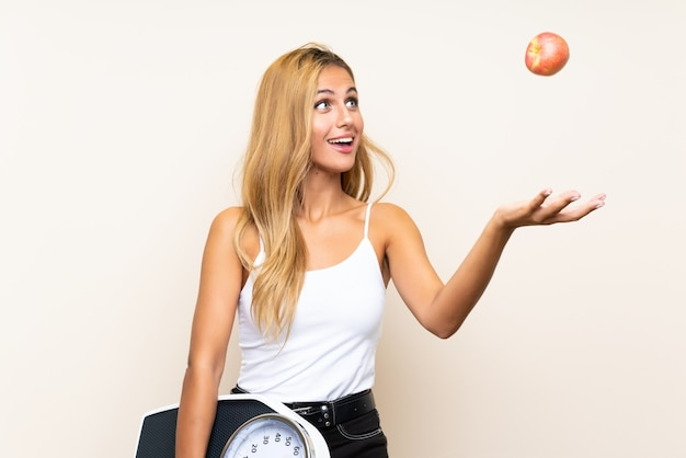 Young blonde woman with weighing machine and with an apple