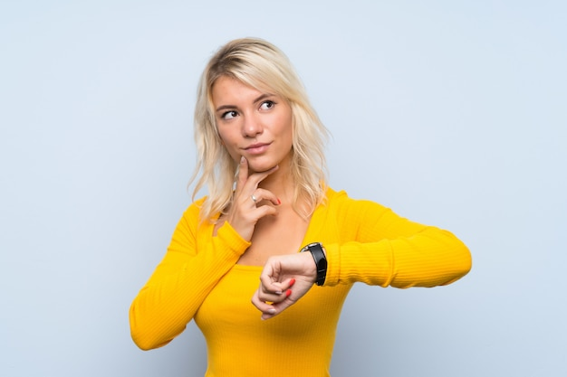 Young blonde woman with wrist watch and thinking an idea