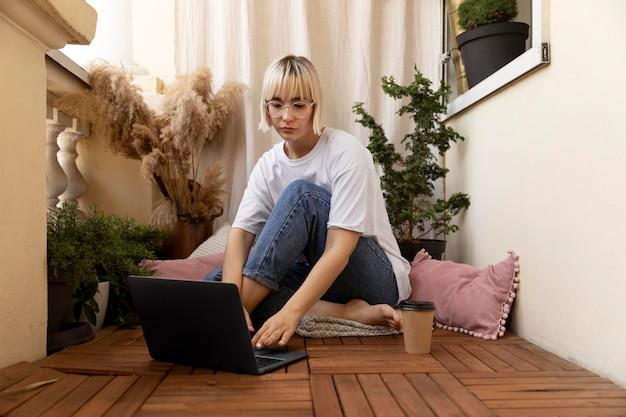 Giovane donna bionda che lavora da casa sul pavimento