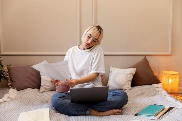 Giovane donna bionda che lavora da casa sul suo laptop
