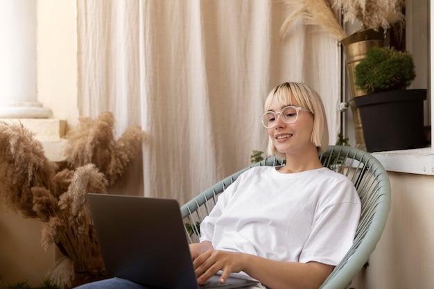 그녀의 의자에 집에서 일하는 젊은 금발의 여자