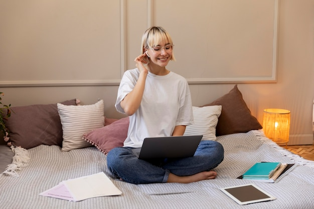 Молодая блондинка работает дома на своем ноутбуке