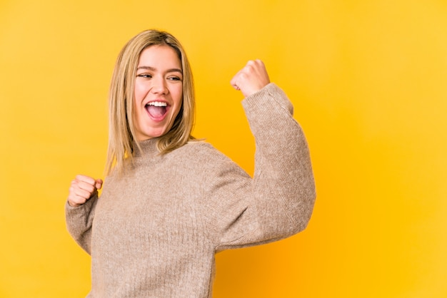 Young blonde woman on yellow wall raising fist after a victory