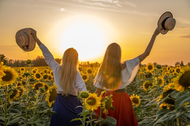 若いブロンドの女性はひまわり畑で夕日を楽しむ