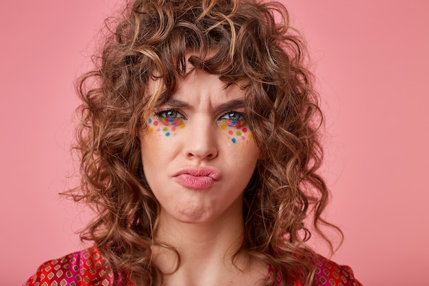 Young blue-eyed woman with brown curly hair and festive makeup looking provocatively and frowning her eyebrows, isolated